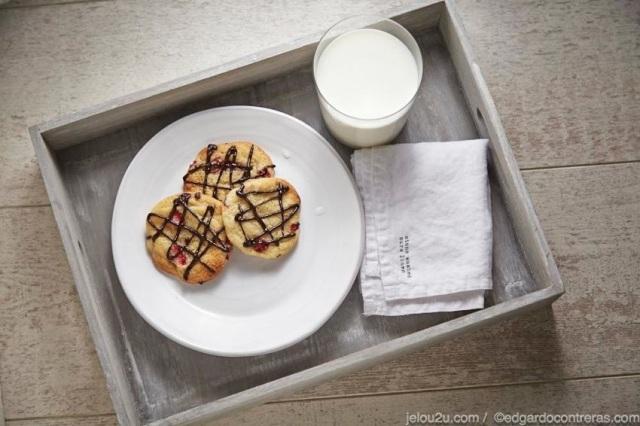 Galletas en plato sobre charola, vaso de leche y servilleta