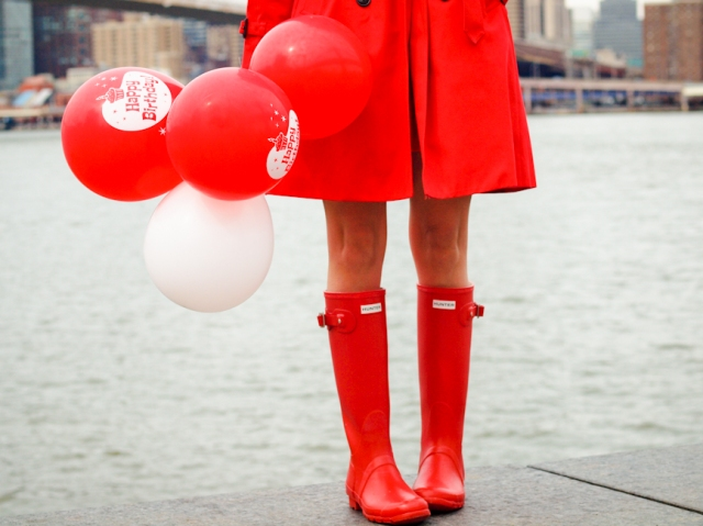 Girl wearing red trench and rain boots with balloons