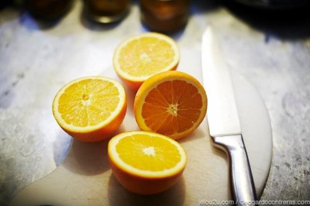 Naranjas cortadas sobre tabla de picar y cuchillo