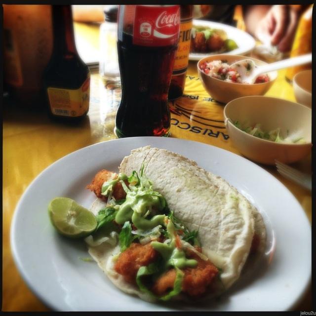 Tacos de camaron sobre plato en mesa