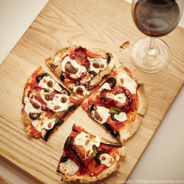 pizza vegetariana con copa de vino